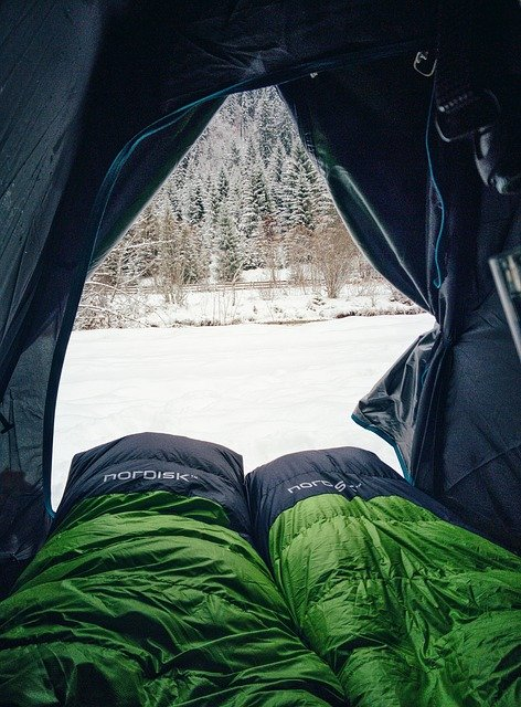 Sleeping bags inside tent with snow outside